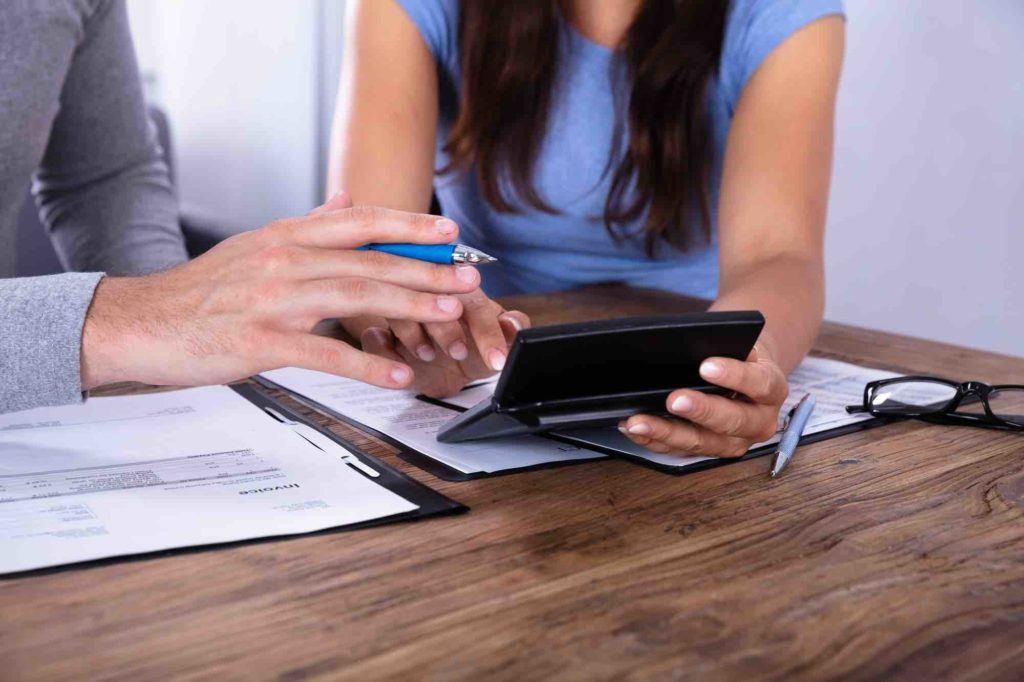 Mann und Frau berechnen mit Taschenrechner den Erbschaftssteuer Freibetrag
