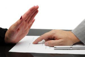 Ablehnende Handung einer Hand bei Vertragsabschluss