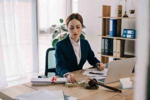 Anwältin mit Geld und Anwaltshammer beim Schreibtisch