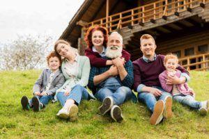 Familie sitzt am Hang vorm Haus