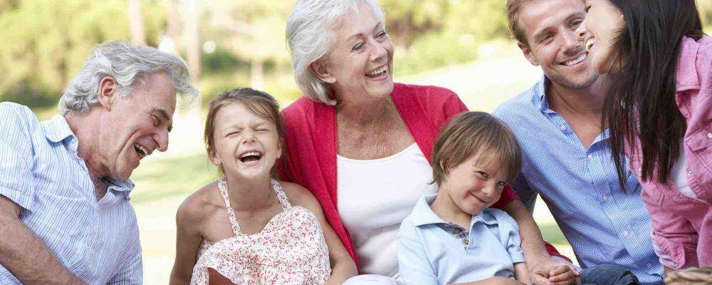 Drei Generationen Familie sitzt im Gras