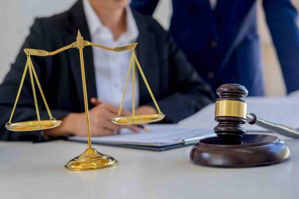 Anwälte sitzen vor Holzhammer bei Gericht