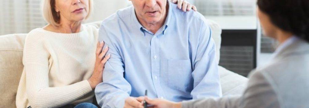 Besorgtes Ehepaar sitzt auf der Couch und unterschreibt Vertrag