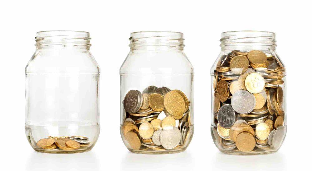 3 Gläser mit unterschiedliche vielen Münzen symbolisieren unterschiedliche Erbschaftssteuer Freibetrag Höhen