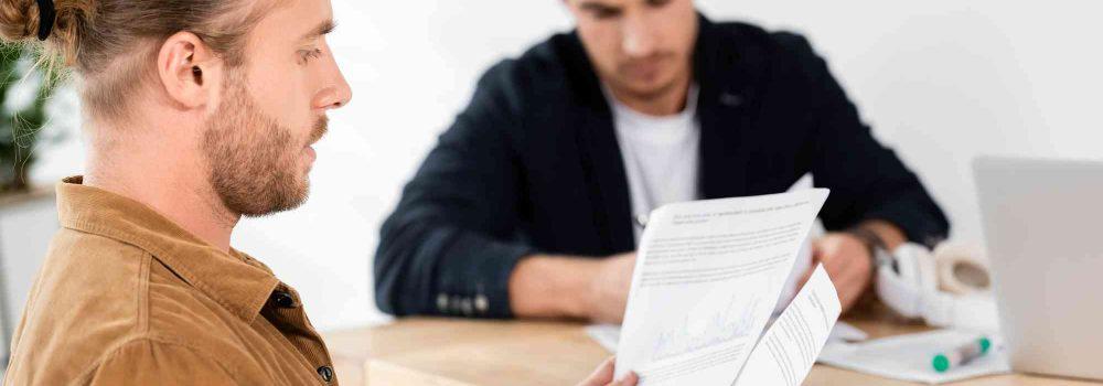 Mann sitzt neben einem Tisch und hält Vertrag in der Hand