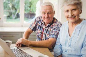 Älteres Ehepaar sitzt vor dem Laptop