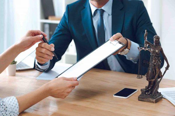 Anwalt reicht Frau ein Blatt Papier