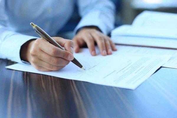 Mann unterzeichnet beim Anwalt einen Erbvertrag