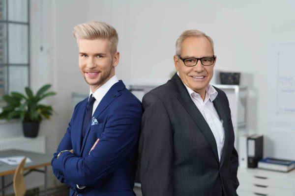 Vater und Sohn stehen im Unternehmen Rücken an Rücken